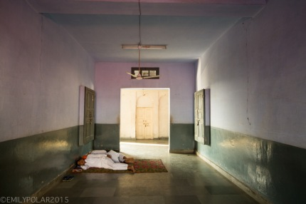 Two Indian men napping on the floor in a hallway near the Golden Temple.
