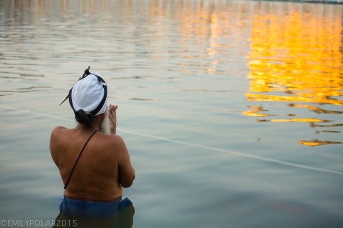Indian man with turban stands in the water with hands in prayer at the Golden Temple.