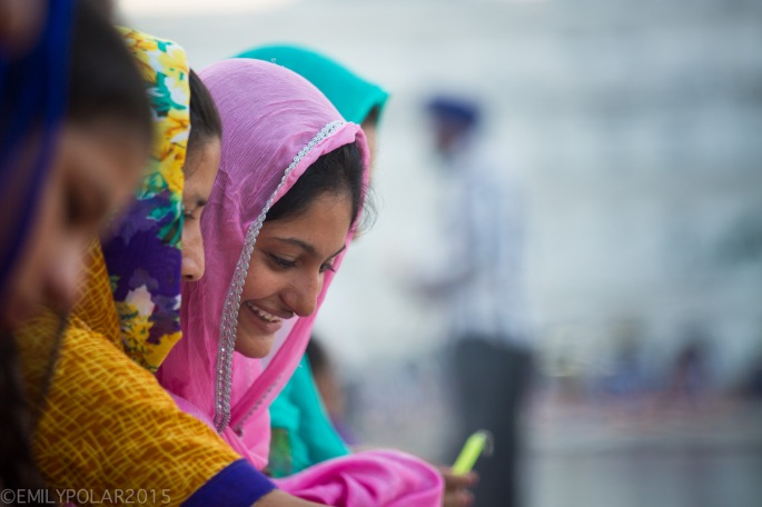 Indian woman wearing her pink sari over her head smiling while lighting candles at Diwali.