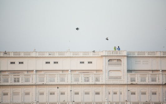 Two Punjabi men stand on top floor of the white complex at the Golden Temple.