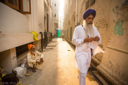 Punjabi man with turban walking down a golden alley with the sun shinning on his back.