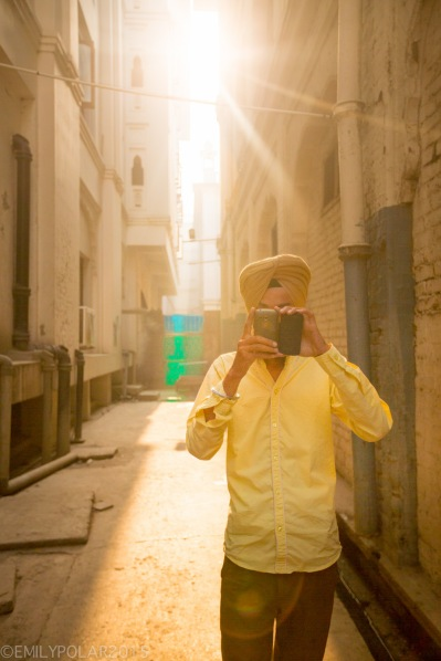 Young Punjabi man wearing a yellow turban and shirt taking a photo with smart phone in sunlit alley in Amritsar.