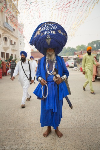 Sikh man wearing traditional blue with sword and huge turban standing barefoot in the streets of Amritsar near the Golden Temple.