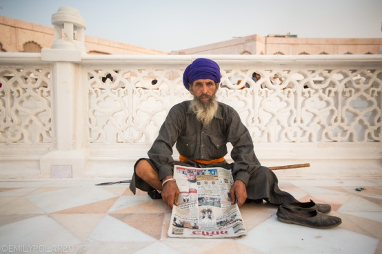 Indian man takes a break from reading his newspaper looking up at the camera for a portrait at the Golden Temple, Amritsar.