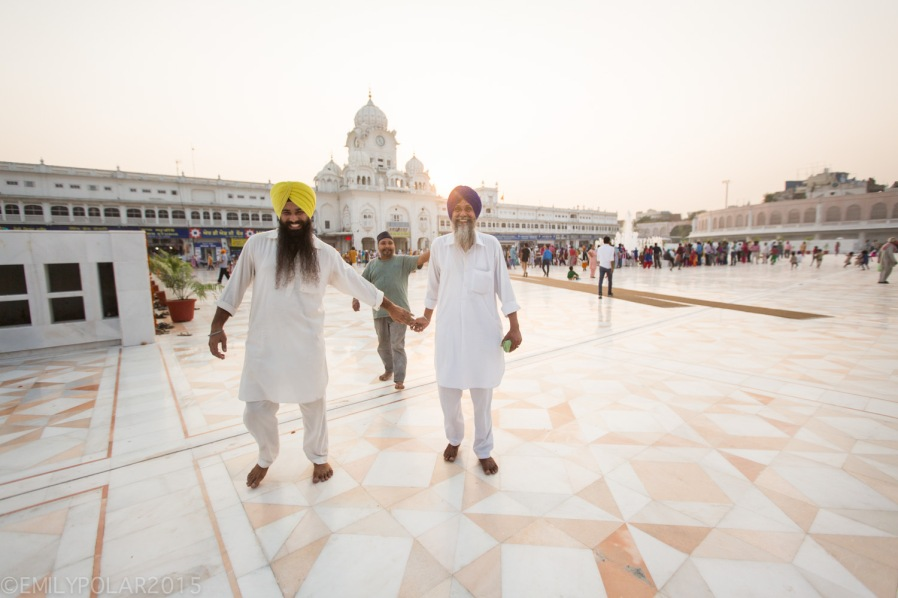 Two Indian men dressed in white walking outside the grounds at the Golden Temple holding hands and smiling.
