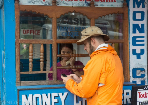 Western man changing U.S. Dollars to Nepalese Rupee in Pokhara, Nepal.