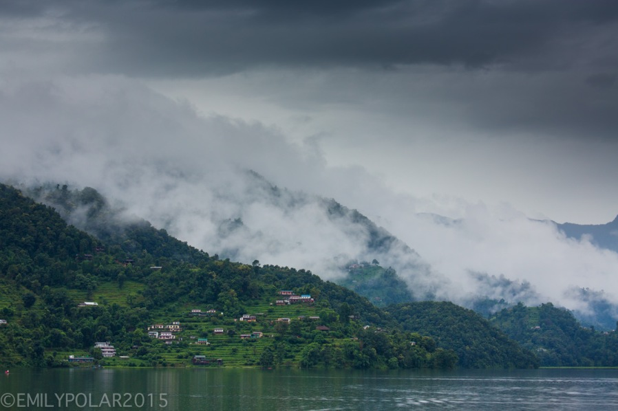 Low clouds roll in hugging the terraced hillsides along Pokhara Lake, Nepal.