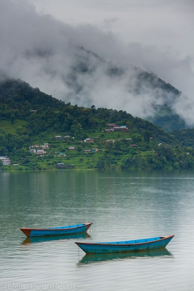 Cute wooden boats floating on Pokhara lake with locals paddling tourists around on a cloudy day in Pokhara, Nepal.