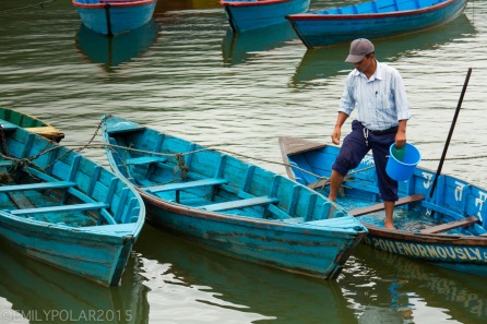 Nepali man pouring water out of his small wooden boat on Pokhara Lake.