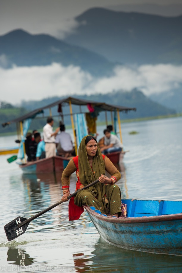 Hindu woman paddling blue wooden boat across Pokhara Lake in Nepal.