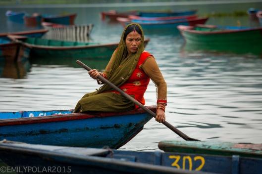 Hindu woman paddling blue wooden boat across Pokhara Lake in Nepal.