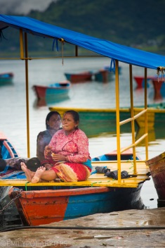 Nepali woman on a boat on Pokhara Lake lighting up a cigarette.