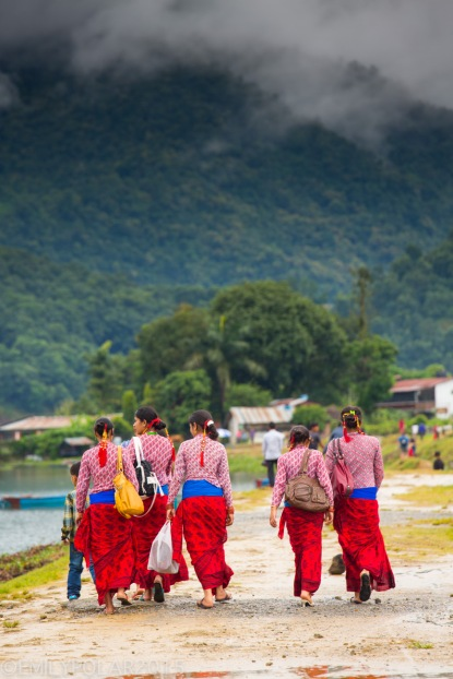 Nepali women dressed up in traditional red clothing for morning ceremony near Pokhara Lake, Nepal.