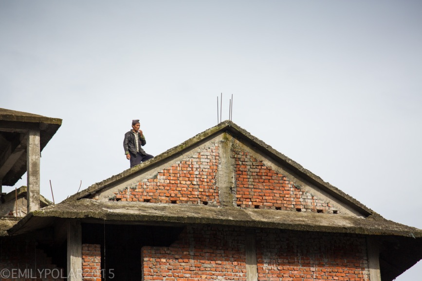 Nepali man standing on a roof top of a brick home in Pokhara.