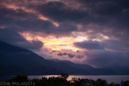 Low clouds roll in at sunset hugging the terraced hillsides along Pokhara Lake, Nepal.