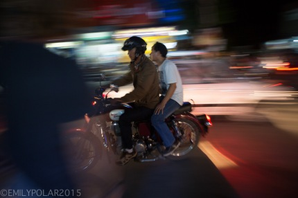 Nepali men cruz by on a motorcycle at night in the streets of Pokhara, Nepal.