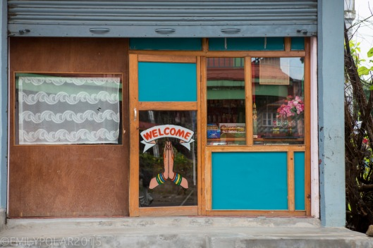 Welcome sign painted on glass door with hands in prayer at a shop along the streets in Pokhara, Nepal.