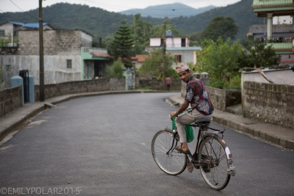 Nepali man riding his bicycle down the street in Pokhara.