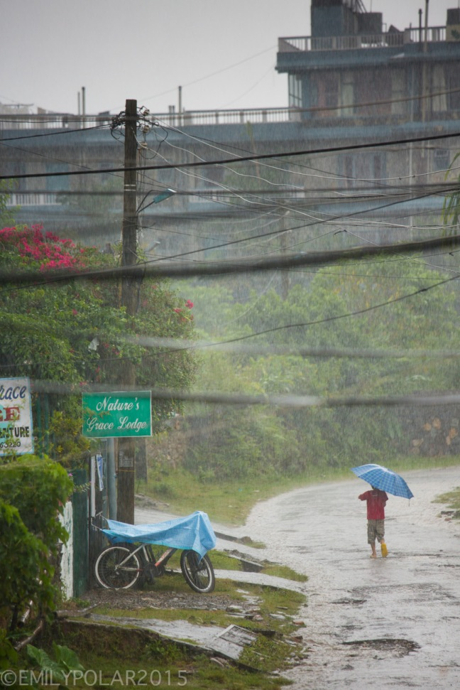 Man walking with umbrella in the raining streets of Pokhara.
