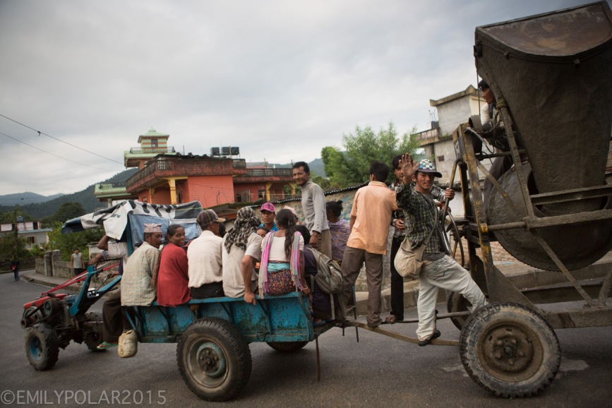 Nepali men and women riding in a trailer with construction equipment down a street in Pokhara.