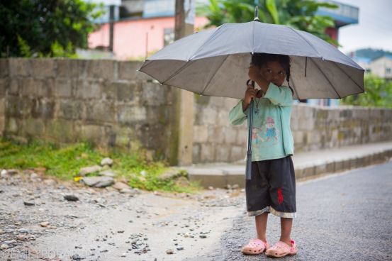 Young Nepali girl standing in the streets of Pokhara with an umbrella.