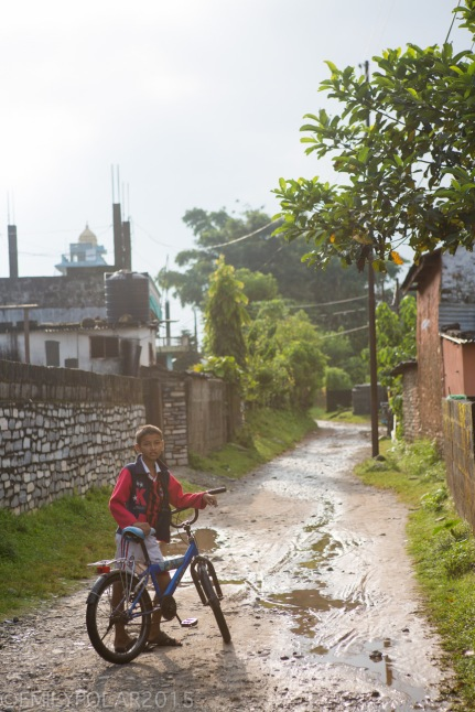 Young Nepali boy with his bicycle standing on a muddy dirt road in Pokhara.