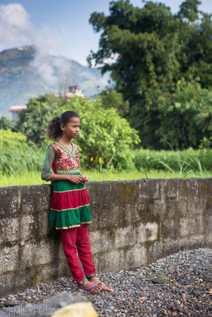 Young Nepali woman standing along a cement fence near her home wearing traditional colorful clothing.