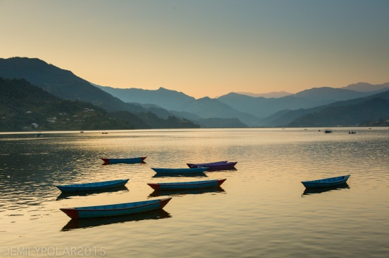 Wooden boats resting on Pokhara Lake in the Himalayas of Nepal.