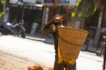 Nepali man throwing red bricks in a woven basket carrying with a head strap while working street construction in Pokhara.