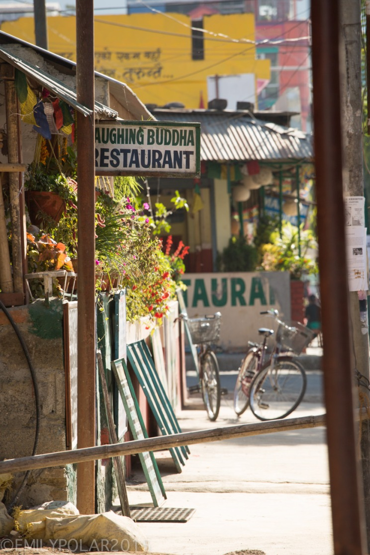 Street view of Laughing Buddha Restaurant sign in Pokhara with bikes in the background.