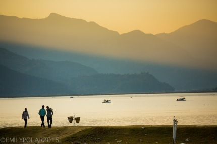 Tourists walking along the shore of Pokhara lake in the golden light at dusk.