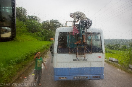 Nepali grabbing his bags from the top of a bus in the rain along the road in rural Nepal.