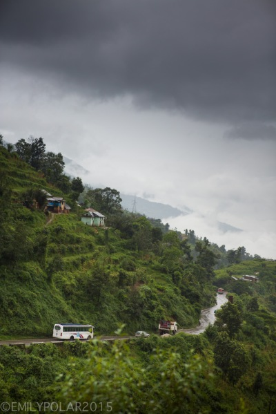 Curvy road winding from Kathmandu to Pokhara through the green lush and rainy hillside of Nepal.
