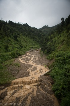 Muddy rain water flowing down rocky run off stream on the way to Pokhara, Nepal.