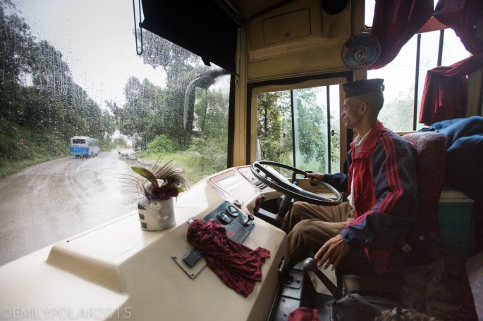 Nepali bus driver turning the big wheel steering us through the rain and mud.