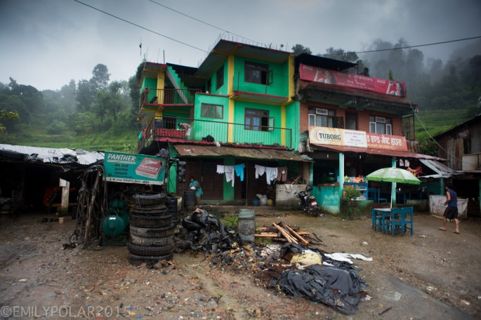 Brightly painted home with tires and a compressor off side of the road to Pokhara in rual Nepal.