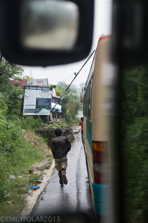 Nepali man running down the wet street along buses waiting in traffic.