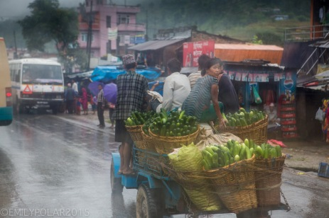 Nepali men and woman ride down the road in the rain in a cart full of woven baskets of vegetables.