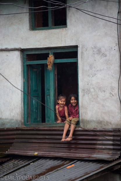 Cute Nepali girls sitting in a window smiling during a rain storm along the road to Pokhara, Nepal.