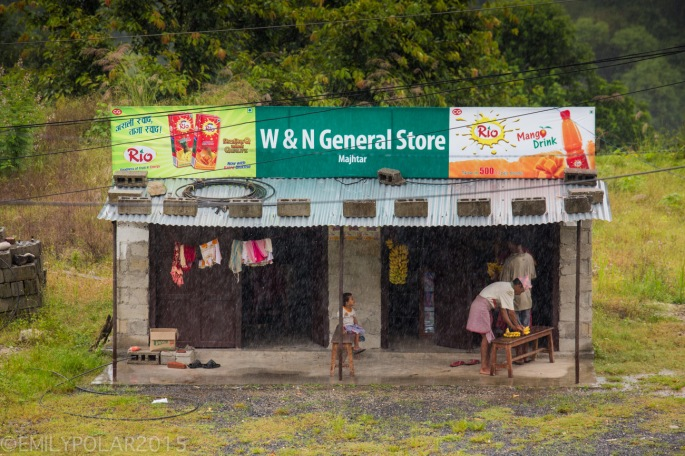 Small general store with tin roof and juice advertisements in rural Nepal.