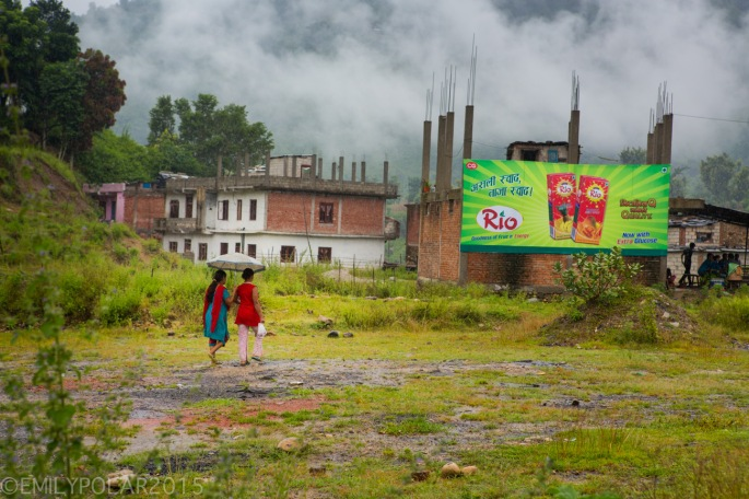 Nepali women walking through a wet field with an umbrella below a juice billboard.