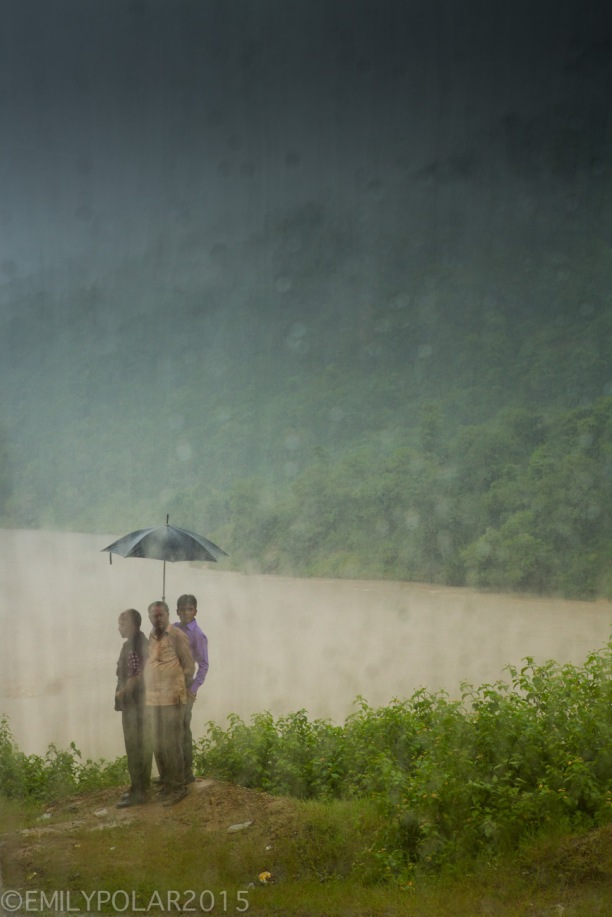 Nepali men standing on the side of the road to Pokhara in the rain holding an umbrella.