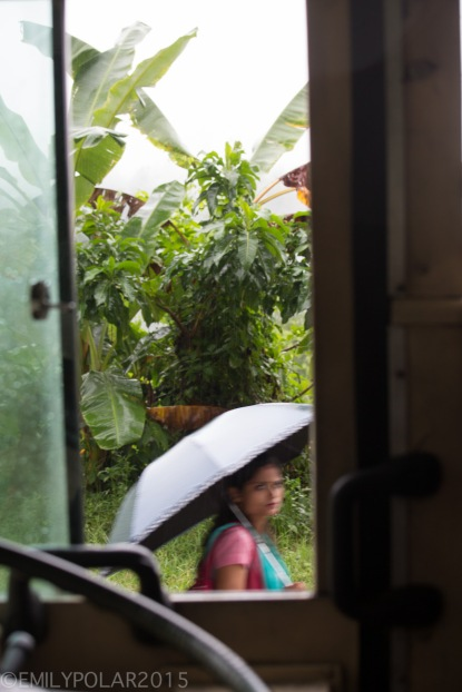 Nepali woman passing an open bus window with an umbrella on the road to Pokhara.
