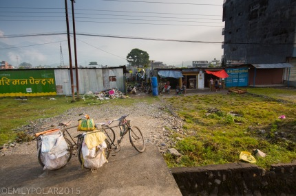 Two bicycles parked with bags attached to the back to pick up and deliver items in Nepal.