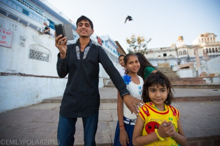 Indian father with daughters taking a picture with his smart phone at Pushkar lake in Rajasthan.
