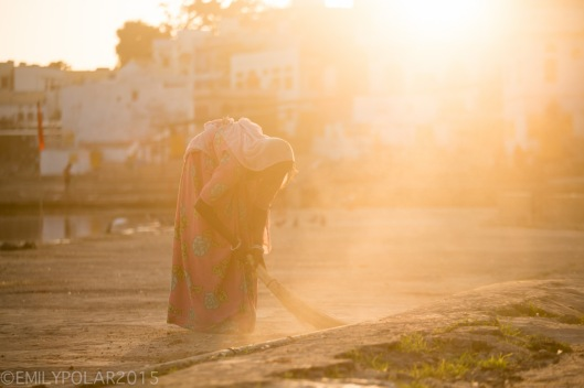 Indian women wearing colorful saris sweeping with straw broom in the dusty back lit sunset at the ghats at Pushkar Lake in Rajasthan, India.