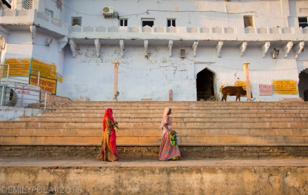 Indian women wearing colorful saris carry straw brooms and dust pans to clean the ghat at sunset in Puskar.