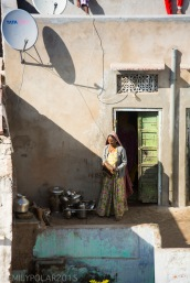 Indian woman at her home next to steel dishes and her doorway in the morning sun of Pushkar.