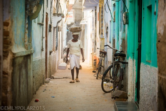 Rajastani man walking down alley carrying dirt on top of head in basket in Pushkar, India.