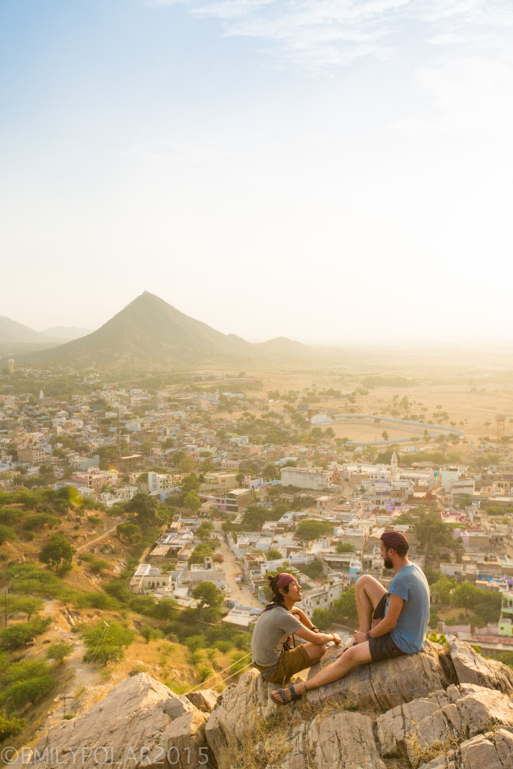 Tourists sitting on a rock watching the sunset on hill at Temple above Pushkar in Rajasthan.
